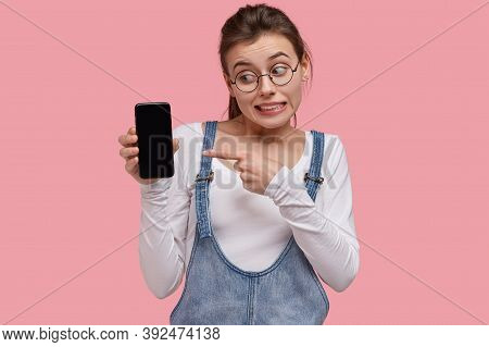 Photo Of Emotive Young Woman Points At Screen Of Modern Gadget, Hesitates Whether To Buy Smart Phone