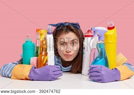Horizontal Shot Of Indignant Young Woman Does Housework, Raises Eyebrows And Looks Surprisingly At C