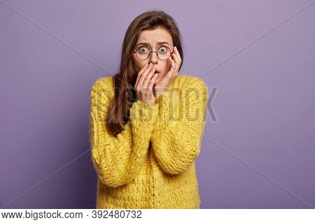 Waist Up Shot Of Fearful Shocked Stupefied Young Woman Covers Mouth, Has Eyes Popped Out, Dark Hair,