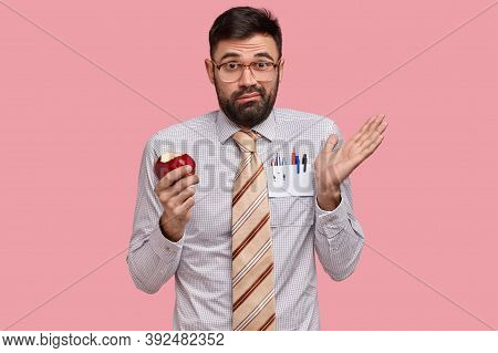 Clueless Discontent Bearded Man Spreads Hand, Holds Red Apple, Wears Optical Glasses And Formal Clot