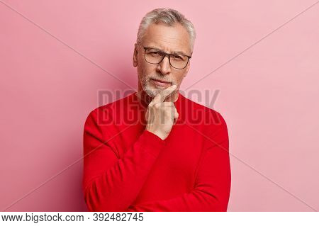 Headshot Of Handsome Grey Haired Man Holds Chin, Dressed In Red Sweater, Looks Directly At Camera, H
