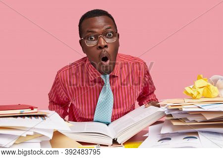 Comic Horrified Black Male Wonk Holds Thick Opened Book, Stares In Stupor, Works On Writing Course P