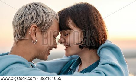 Close Up Of Young Loving Lesbian Couple Hugging Before Kiss While Admiring The Sunrise Together, Sel