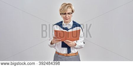Portrait Of Elegant Middle Aged Caucasian Woman Wearing Business Attire And Glasses Holding, Looking