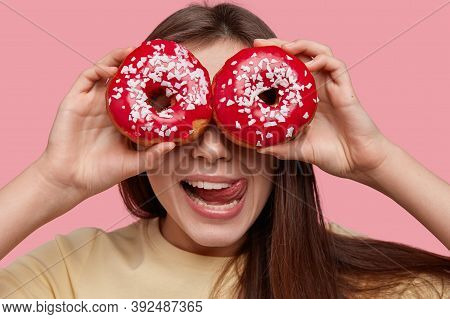 Headshot Of Funny Young European Woman Covers Eyes With Two Glazed Doughnuts, Licks Lips With Tongue
