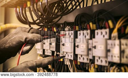 Close-up Hand Of Electrical Engineer Using Measuring Equipment To Checking Electric Current Voltage