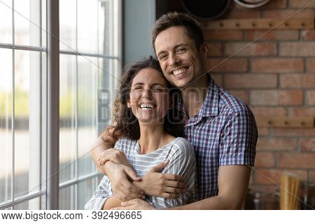 Portrait Of Smiling Couple Renters Enjoy Day In New Home