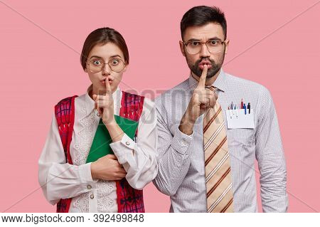 Photo Of Secret Female And Male Have Surprised Expressions, Shows Hush Sign, Keep Fore Finger Over M