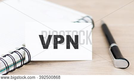 The Vpn Label On The Business Card Is On The Table Next To A Notebook And Pen.