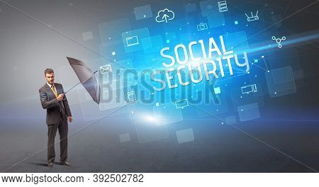 Businessman defending with umbrella from cyber attack and SOCIAL SECURITY inscription, online security concept