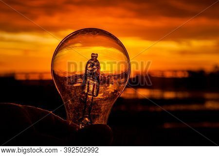Light bulb in hand against sunrise with colorful sky