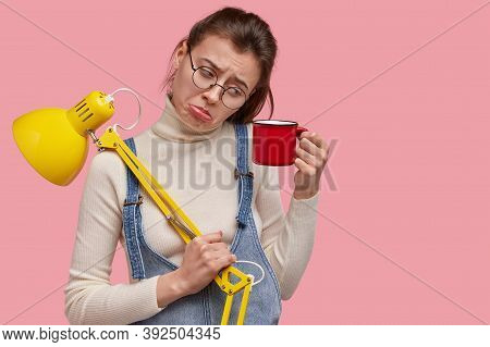 Photo Of Dejected Young Woman Looks In Displeasure On Mug Of Drink, Holds Yellow Desk Lamp, Dressed