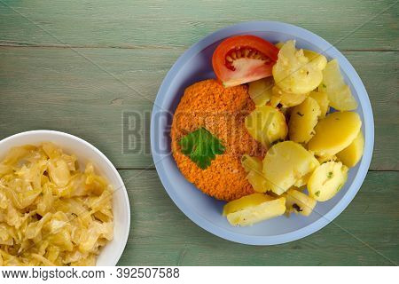 Meatball With Potatoes On Green Wooden Background. Meatball With A Slice Of Tomato On Light Blue Pla
