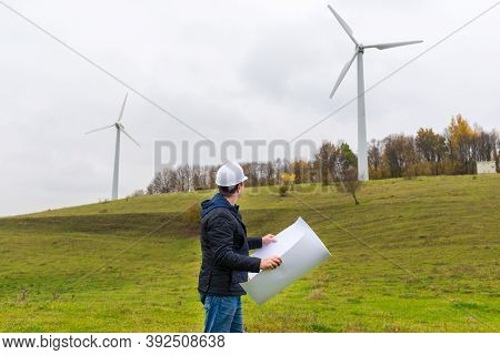 Worker Holds Paper Project Looking At Windmill Of A Windfarm Outdoors Shot.