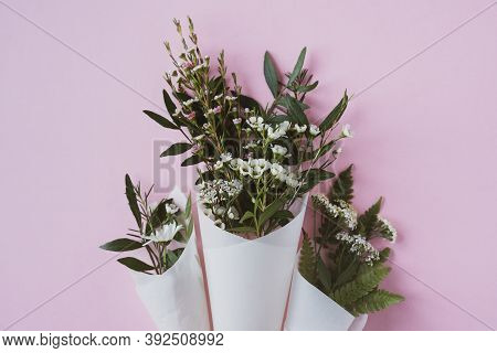 Top View Closeup Of Three Beautiful Bouquets Of Delicate Small White Flowers With Green Leaves In Pa