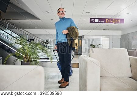 Joyous Man Standing At The Airport Terminal