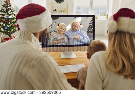 Young Family Staying At Home On Christmas Holidays But Keeping In Touch With Grandparents