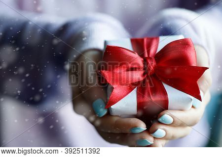 Gift Box With Red Bow In Womans Hands
