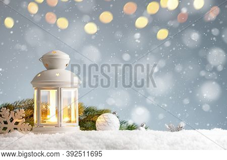 White Lantern With Christmas Decorations In A Snowdrift On Blue Background
