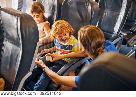Flight Attendant Fastening A Seatbelt Of A Happy Boy