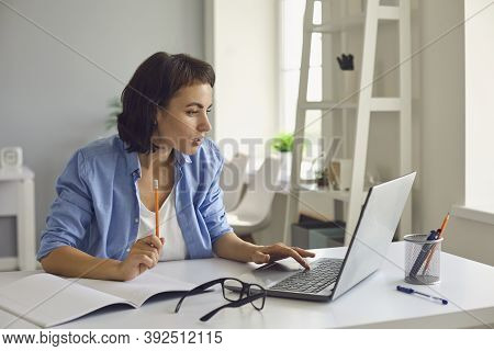 Woman Sitting With Laptop And Notebook, Watching Online Lesson Or Videocall And Making Notes