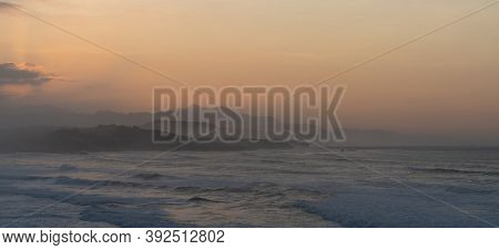 Wild Ocean Coast At Sunset With Waves Breaking And Mountains In Silhouette Behind