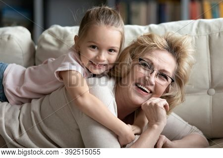 Portrait Of Laughing Devoted Mature Woman Holding On Back Kid.