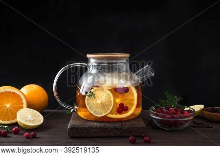 Winter Fruit Tea. Citrus And Berry Tea With Cranberries, Lemon, Oranges  In Glass Teapot On Dark Woo