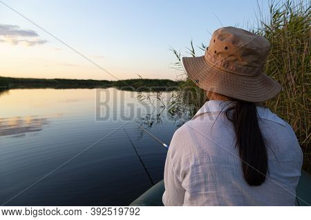Fishing On The Lake. Girl With A Fishing Rod In A Rubber Boat On The Lake Is Fishing. Hobbies, Leisu