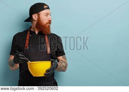 Concentrated Male Cooker Focused Away, Whisks Cream In Yellow Bowl, Mixes Ingredients, Hears Some No