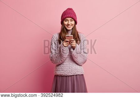 Image Of Happy Positive European Female Holds Mobile Phone In Hands, Waits For Order And Looks At De