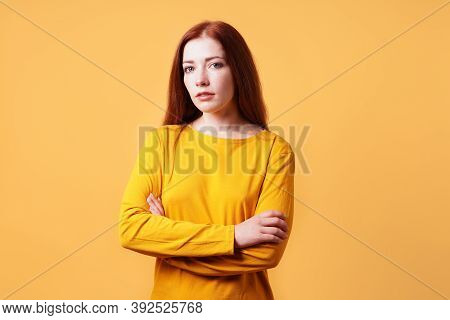 Colorful Studio Portrait Of Confident Young Woman With Her Arms Folded - Yellow Orange Color Backgro