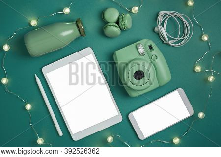 Flat Lay Tablet, Phone, Analog Green Camera And Headphones, Green Bottle And Green Macaroons On Gree