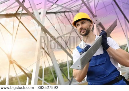 Worker With Detail From High Voltage Tower Construction On Building Site. Installation Of Electrical