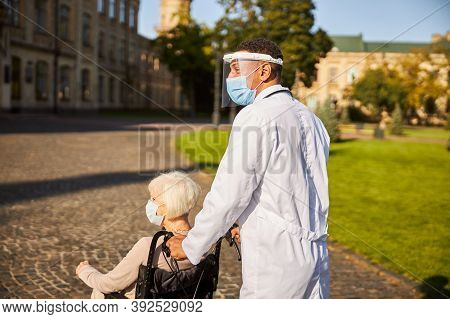 Medical Person Pushing A Wheelchair With A Senior Citizen