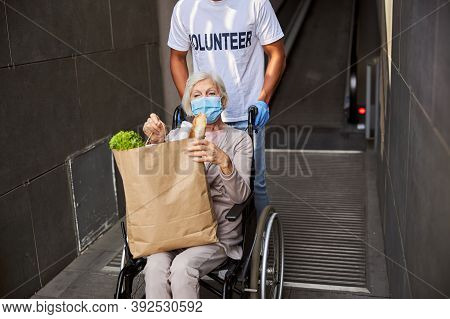 Elderly Person Riding Out Of A Wheelchair Access With Supplies
