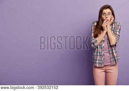 Omg, Its So Spooky. Frightened Worried Lady Has Eyes Full Of Fear, Gazes With Fear, Wears Optical Gl