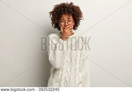 Negative Emotions Concept. Sorrowful Hopeless Ethnic Woman Cries In Despair, Covers Mouth With Hand,