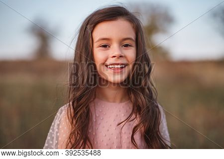 Charming Positive Little Girl With Long Wavy Brown Hair Looking At Camera And Smiling Happily While