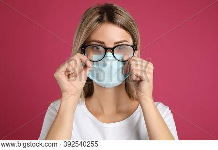 Woman Wiping Foggy Glasses Caused By Wearing Disposable Mask On Pink Background. Protective Measure