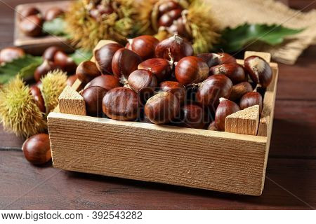 Fresh Sweet Edible Chestnuts In Crate On Wooden Table
