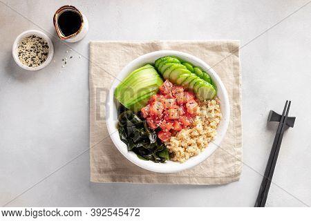 Poke Bowl With Salmon, Quinoa, Wakame Seaweed, Avocado And Cucumber On Gray Background. Trendy Healt