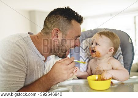 A Little Baby Eating Her Dinner And Making A Mess With Dad On The Side