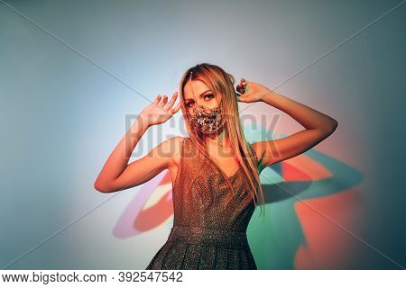 Pandemic Party. Neon Light Portrait. Night Club Look. Glamour Woman In Chain Face Mask Matching Gold