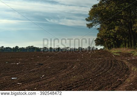Freshly Plowed Field With Plastic Waste In The Ground. Environmental Pollution, Penetration Of Micro