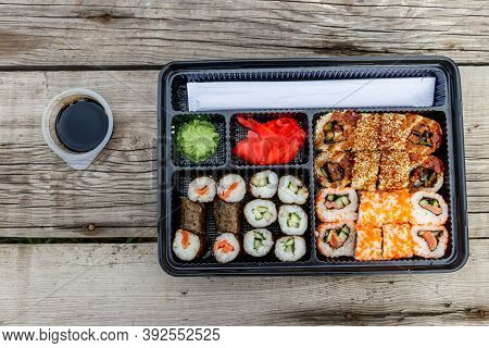 Set Of Sushi Rolls In Plastic Box On Wooden Table. Sushi For Take Away Or Delivery Of Sushi In Plast