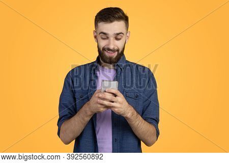 Handsome Bearded Guy With Smartphone Browsing Internet, Communicating Online Or Shopping Over Orange