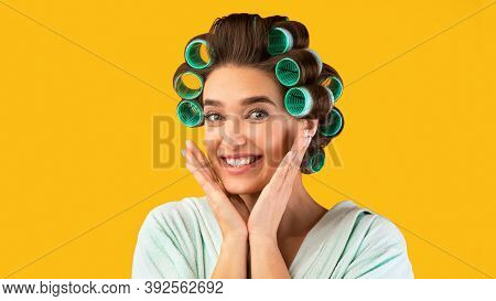 Cute Housewifes Portrait. Pretty Lady With Hair Curlers Posing Smiling To Camera Standing Over Yello