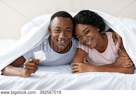 Safety Sex Concept. Young Black Couple Lying In Bed Under Blanket, Hugging And Holding Condom And Sm