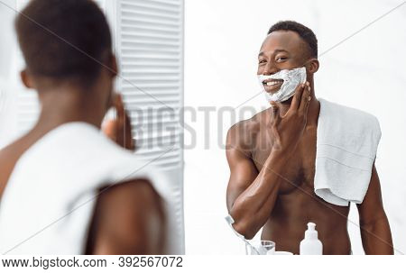 Shirtless African Guy Applying Shave Foam On Face Preparing For Shaving Standing Near Mirror In Bath